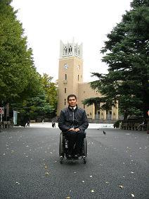 [写真]大隈講堂をバックに、講演前なので緊張している長田選手