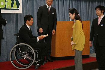 [写真]抽選会で金メダルレプリカをプレゼントする長田選手