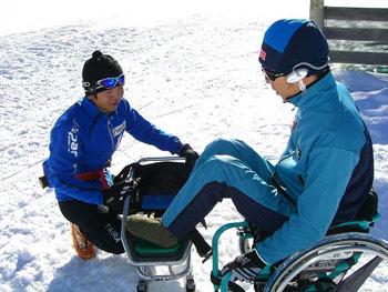 [写真]シットスキーを乗り換える久保選手と、サポートする鉢蝋選手