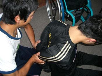 [写真]久保選手のストレッチをサポートする鉢蝋選手