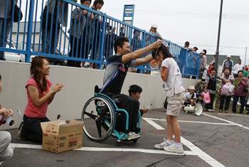 [写真]入賞した子供にお手製のメダルをかける久保選手