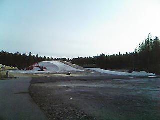 [写真]雪山を崩すショベルカー
