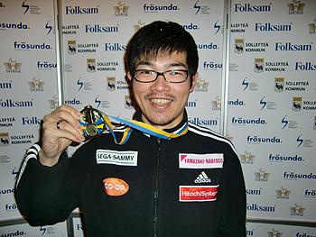 [写真]金メダルを掲げる新田選手