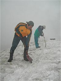 [写真]硬い雪をスコップで削りならしている