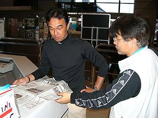 [写真]井口引退記事を読む小林ガイドと渡辺総務