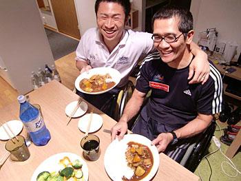 [写真]完成したカレーと笑顔の長田弘幸と久保恒造