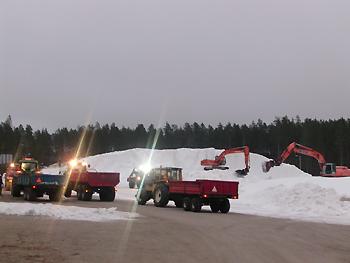 [写真]1年間貯蔵されていた雪を削って運んでいる