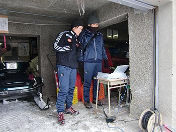 [写真]デジタル銃の弾痕をパソコンで見る阿部コーチと勝呂スタッフ