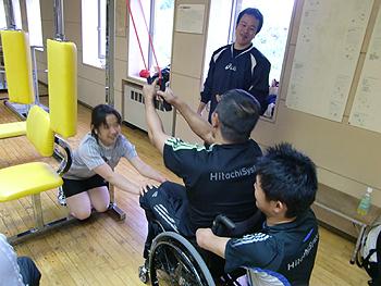 [写真]長田選手の車いすをみんなで押さえる