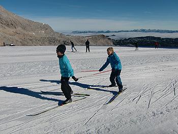 [写真]電車ごっこのようにスキー練習する小学生