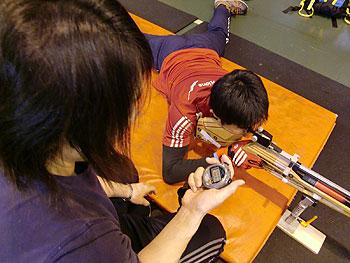 [写真]ライフルを構えている新田佳浩とタイムを計る阿部コーチ