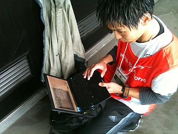 [写真]レースの速報を調べる勝呂事務局員