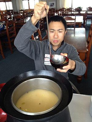 [写真]味噌汁をつぐ久保選手