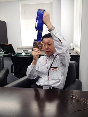 [写真]メダルを見つめるスキー部石川部長