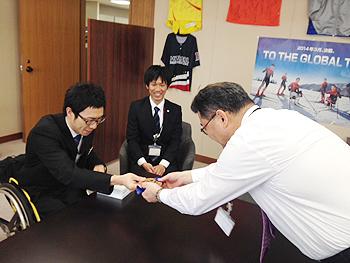 [写真]久保選手が佐久間社長に報告