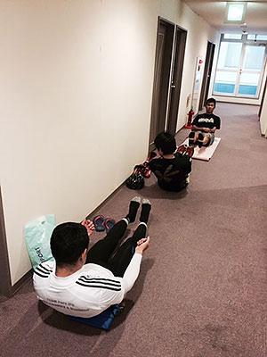 [写真]廊下で補強トレーニングする選手たち
