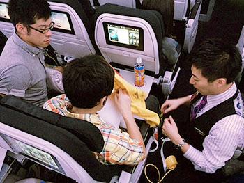[写真]乗務員の方から個別に救命胴衣の説明を受ける高村和人選手