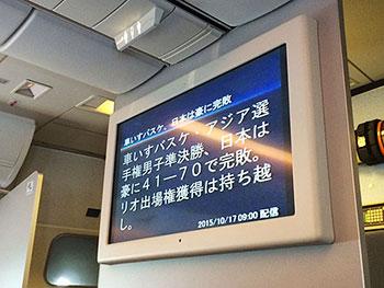 [写真]車いすバスケットボールの試合結果が流れる飛行機内のニュース