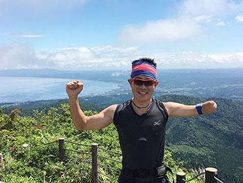 [写真]海の見える山頂に立つ新田佳浩選手