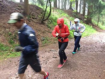 [写真]山間走する佐藤勇治コーチと女子チーム