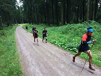 [写真]新田佳浩選手を先頭にスキーポールジャンプする選手たち