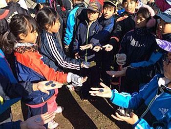 [写真]リオパラリンピック記念コインを掌にのせた子どもたち