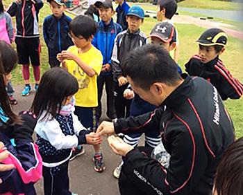 [写真]子供たちにリオパラリンピック記念コインを配る久保恒造選手