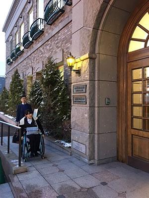 [写真]石屋製菓様入口のスロープを上がる新田のんの選手