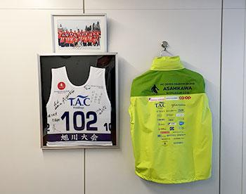 [写真]株式会社TACホールディングス様の応接室に飾られたワールドカップ旭川大会のボランティアジャケットとビブ、ソチパラリンピック日本代表チームの記念写真