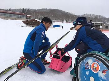 [写真]新しいスキー板を取り付けようとする新田佳浩選手と新田のんの選手