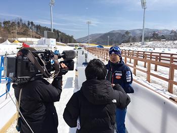 [写真]NHKニュースの取材を受ける新田佳浩選手