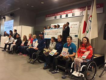 [写真]札幌大学の学生ボランティアが作成した記念色紙を持つ選手たち