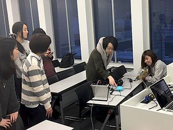 [写真]ブラインド用のビームライフルを体験する学生たち