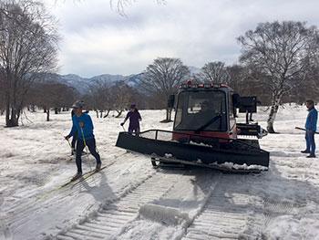 [写真]圧雪車でコース整備する横山さん