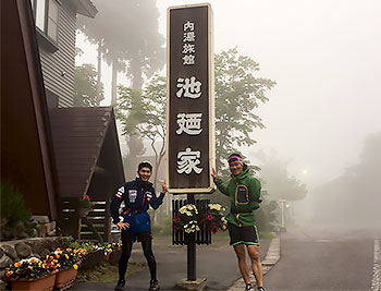 [写真]池迺家の看板の脇に立つ岩本選手、新田選手