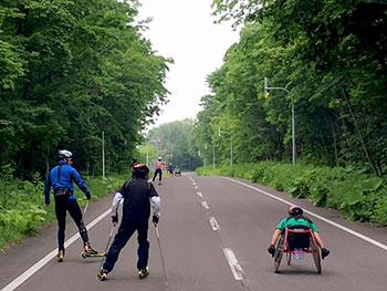 [写真]ローラースキーでトレーニングする高村和人選手とレーサーでトレーニングする新田のんの選手