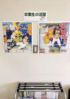 [写真]OBの活躍が掲載された新聞が貼られた大学の掲示板