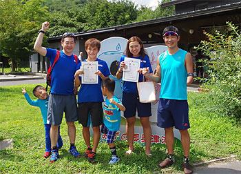 [写真]賞状を持った新田、阿部、川除選手、長濱コーチ、新田選手の子供たち
