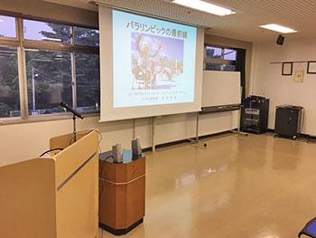 [写真]投影された講演用スライド「パラリンピックの最前線」