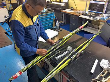 [写真]スキー板ジョイント部分を見る飯星さん