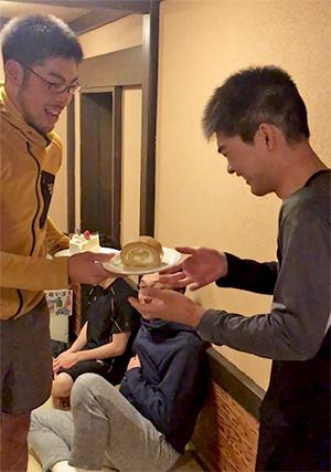 [写真]藤田佑平ガイドからケーキを受け取る岩本啓吾くん