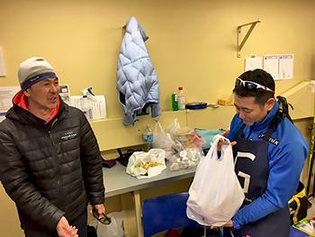[写真]川野さんとパンの差し入れをもらう長濱コーチ