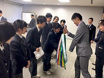 [写真]足立区千寿桜堤中学校の見皆さんから千羽鶴を受け取る新田選手