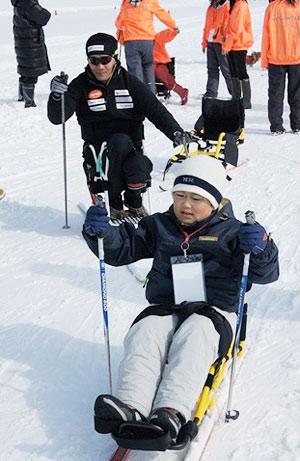 [写真]第1回スキー教室でシットスキー初体験の子供と長田弘幸選手