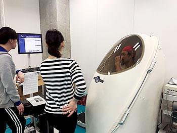 [写真]カプセルの中に入り体脂肪を測定中の馬場選手