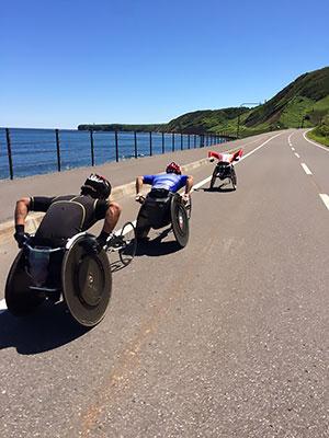 [写真]車道をレーサーで走る洞ノ上選手、渡辺選手、久保選手