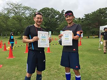 [写真]それぞれの賞状を持って立つ新田佳浩選手と長濱一年