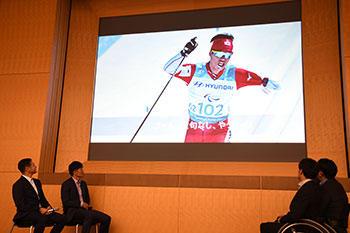 [写真]活動報告会にて平昌での活躍を伝える映像を見る監督、選手たち