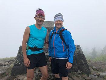 [写真]気温15度前後の根子岳山頂でTシャツ姿の新田選手と長濱監督