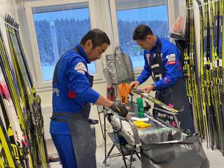 [写真]選手のスキー板を手入しサポートするスタッフ